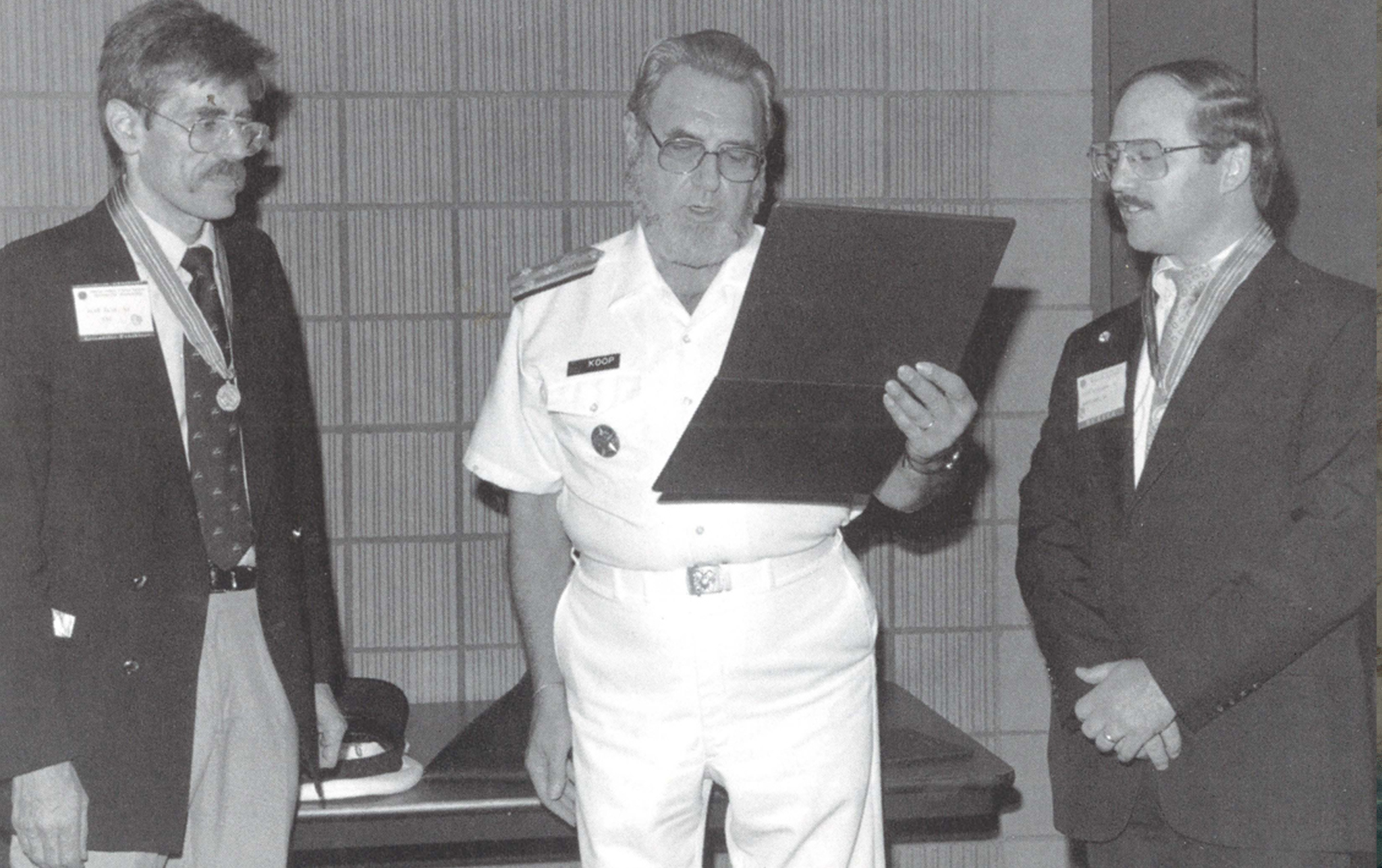 Dr. C. Everett Koop presents Drs. Rick Richards and Alan Blum with the Surgeon General's Medallion, 1988