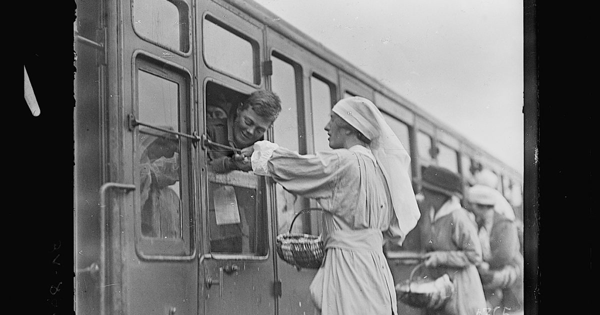 Souilly Meuse France. Miss Winifred Bryce of 294 Henry Street Brooklyn N.Y. giving gum and cigarettes to wounded soldiers on a hospital train.